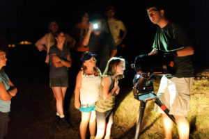 A kid looks through a telescope during Universe in the Park