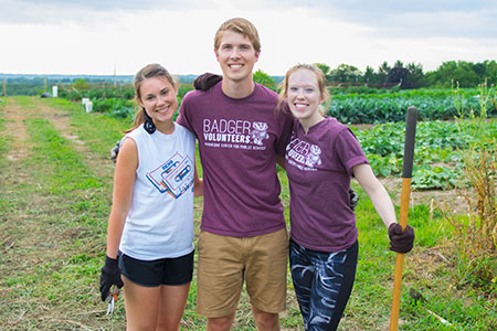 Three Badger Volunteers members pose in front of a garden. Two are wearing maroon shirts that say Badger Volunteers.