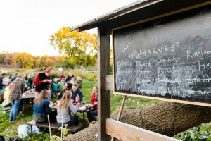 A chalkboard shows different vegetables harvested from the garden, while students sit around a picnic table in the background enjoying a meal.