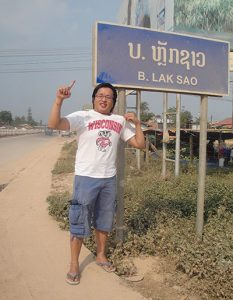 """Pao Vue stands by a sign that says """"Laksao"""" wearing a Wisconsin Badgers t-shirt."""