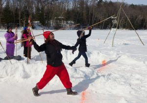Elementary and middle school aged students throw spears toward a target in a snowy landscape.