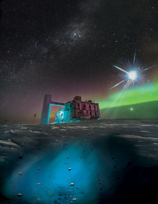 The IceCube lab at the South Pole with aurora in the background