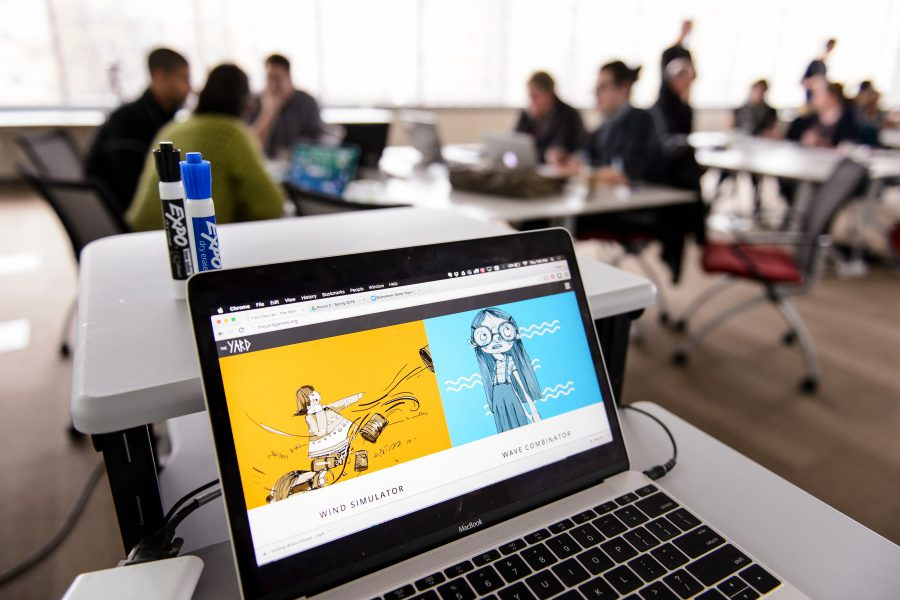 An open laptop showing a developed computer game sits in the foreground, with people talking around work stations in the background.
