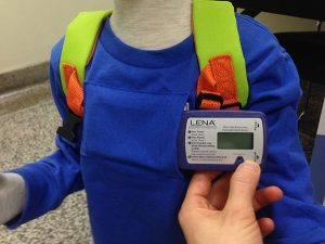 A small device held beside a pocket sewn into the front of a child's shirt meant to hold it