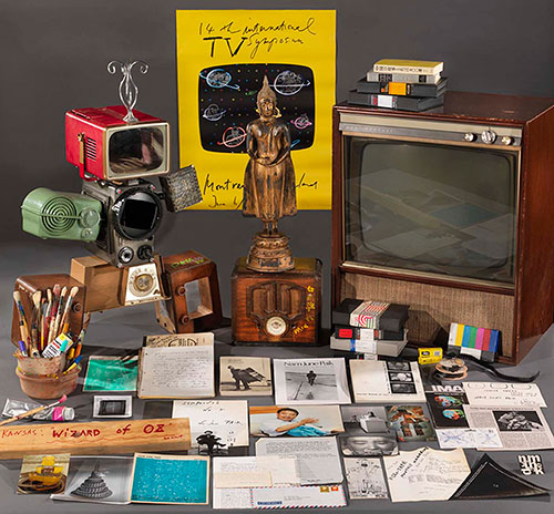 Papers, figures, and old technologies including a television set that are part of the Nam June Paik archive collection are displayed.