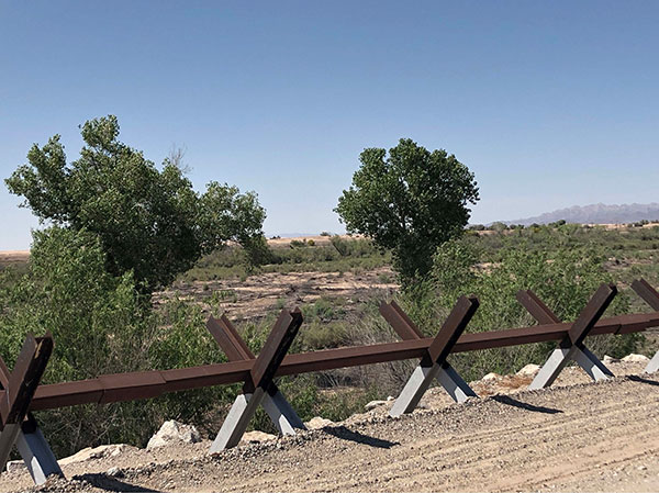 A fence runs along a gravel path, with trees growing along a strip of land in the background.