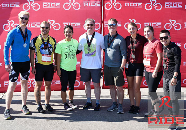 Eight members of the 2018 Medical Physics team in front of a red The Ride background