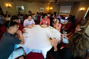 Students sit around a table and chat at a Multicultural Graduate Network event
