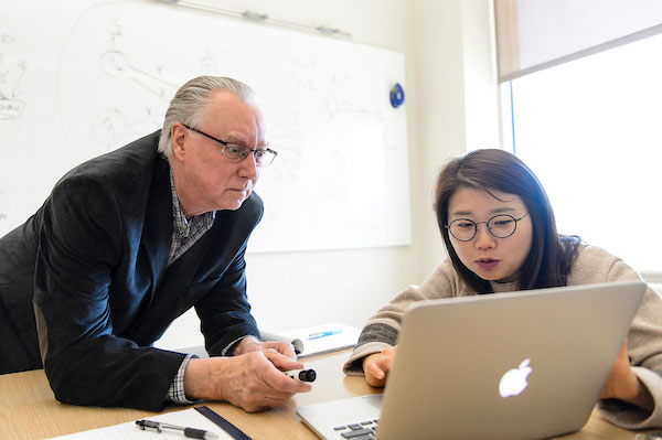 An advisor and graduate student work on a laptop