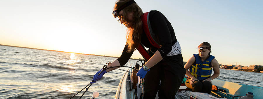 Two graduate students on a boat in Lake Mendota take water samples