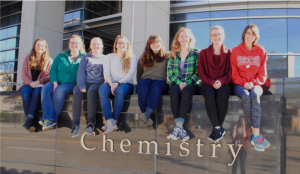 """Eight students sit on a half wall that says """"Chemistry"""""""