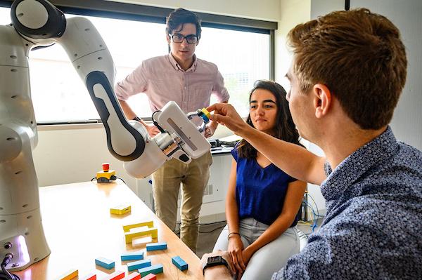 Three graduate students work together on a robotics project