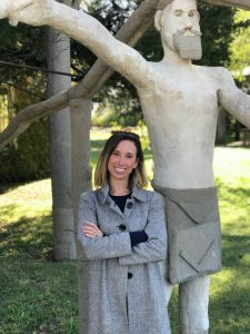 Cortney Anderson Kramer stands in front of a concrete statue of a person