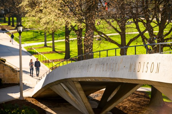 Two people walking on campus near a bridge that says University of Wisconsin-Madison