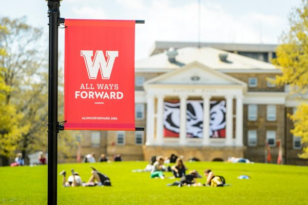 A red banner with a W is shown in front of Bascom Hall, where students sit outside and study