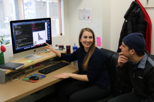 Kirsten Gotting points to a computer monitor. Another person sits next to her and is looking at the same monitor.