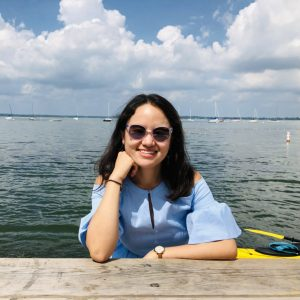 Mengyao Niu poses for a photo in front of Lake Mendota. She is wearing a blue shirt and sunglasses.