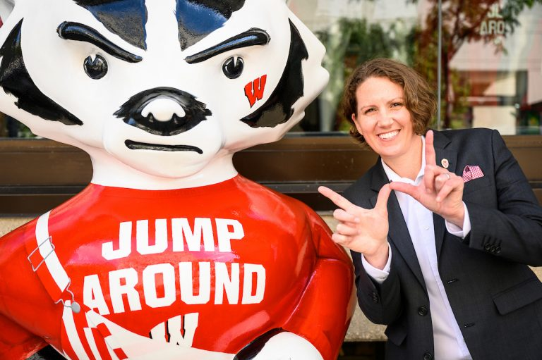 Dean of Students Christina Olstad makes a W sign with her hands. She is standing next to a statue of Bucky Badger and smiling.