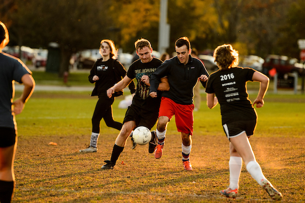 A group of students play soccer on a grassy field.